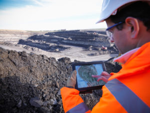 Ecologist using digital tablet surveying surface coal mine site, elevated view --- Image by © Monty Rakusen/cultura/Corbis